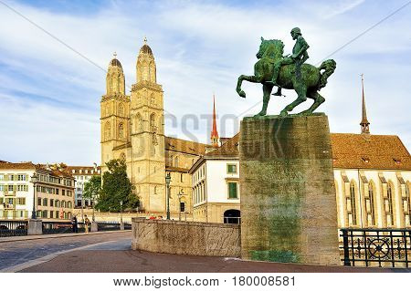 Zurich Switzerland - September 2 2016: Hans Waldmann monument at Munsterbrucke bridge and Grossmunster Church in Zurich Switzerland. People on the background