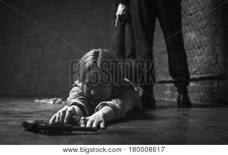 No way I give up. Stubborn strong able girl wanting protecting herself and stretching her hands to a gun while her kidnapper standing behind
