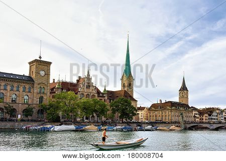 Man in a boat Fraumunster Church and St Peter at Limmat River quay in the city center of Zurich Switzerland.