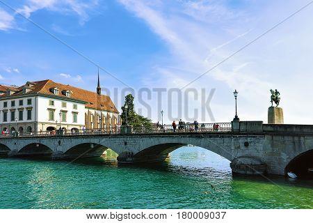 People At Munsterbrucke Bridge Over Limmat River In Zurich