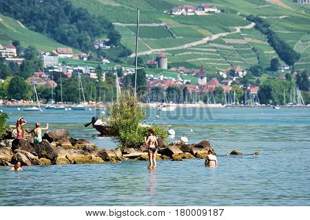 People Swimming And Sunbathing At Lakefront Of Lausanne