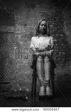 Imprisoned for ransom. Powerless desperate anxious woman being kept somewhere dark against her will and sitting tied up to a chair feeling desperate