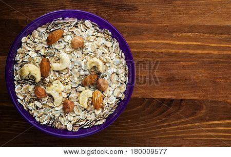 Oatmeal With Nuts(hazelnut, Cashew, Almonds). Oatmeal On A Wooden Table. Oatmeal Top View. Healthy F