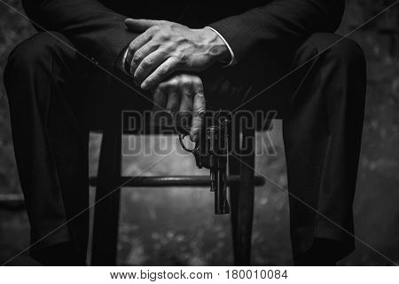 Better not irritate me. Dangerous aggressive mighty man sitting on a chair wearing stylish suit and blackmailing his business rival