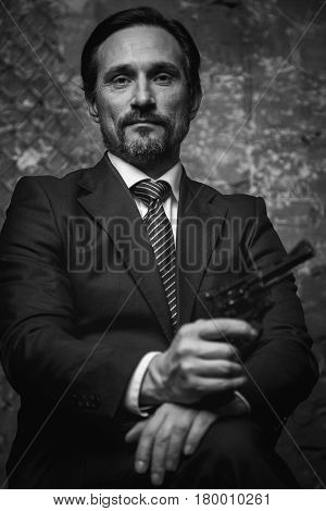 Update of evil. Handsome arrogant charismatic man sitting in some dark place and holding a gun in his hand while looking dangerous