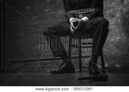 This is my chance. Restless anxious captured man looking at the gun lying nearby while being imprisoned and chained up to a chair