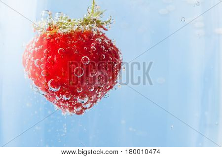 Close up of a bright red fresh strawberry with green leaves flloating in light blue sparkling water and covered in bubbles. Copy space to right.