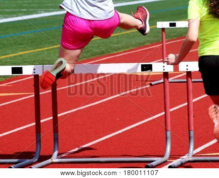 A female track and field athlete in flight over a hurdle on a red track