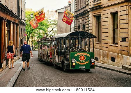 People In Excursion Tram At Street With Flags At Geneva