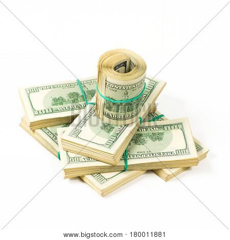 A twisted bundle of 100 dollar bills stands on packs of dollars. Isolated on white.