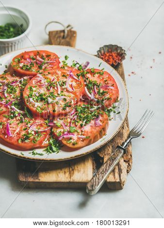 Fresh heirloom tomato, parsley and onion salad in white plate on wooden board over light grey marble background, selective focus. Clean eating, vegan, vegetarian, healthy, dieting food concept