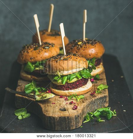 Healthy vegan burger with beetroot and quinoa patty, arugula, avocado sauce, wholegrain buns on rustic wooden board over dark table, selective focus, square crop. Clean eating, dieting food concept