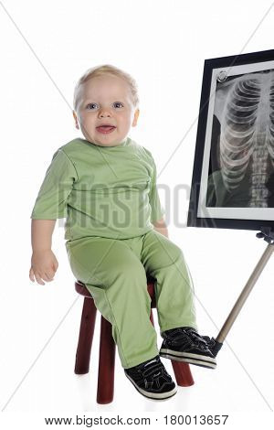 An adorable toddler boy playing x-ray technician, with a chest x-ray in the background.  Isolated on white.