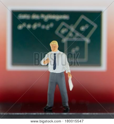 Man stands in front of chalkboard. Plastic puppet man in white shirt and grey trousers. Teacher explaining math theory. Learning physics. School education concept image. Doll teacher in formal wear