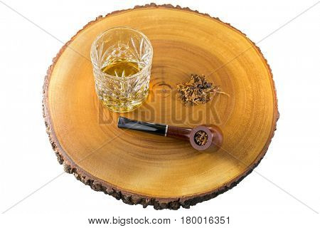 Glass of single malt scotch whisky next to aromatic pipe tobacco on wood isolated on white background