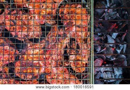 Grilled meat on coals closeup photo. Red meat barbecue cooking. Outdoor grill with pork ribs. Juicy meat food. Summer picnic banner template. Tasty pork BBQ. Brown pork chops baked on fireplace image