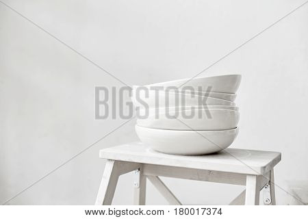 White empty ceramic plates stand in a pile stand on a wooden stool kitchen equipment