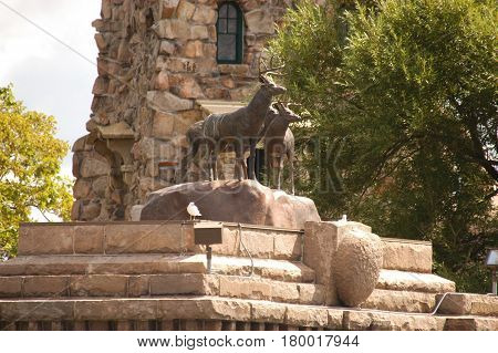 deer buck  statue stone arch window tree