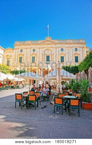 People Resting At Open Air Cafes In Republic Square Valletta