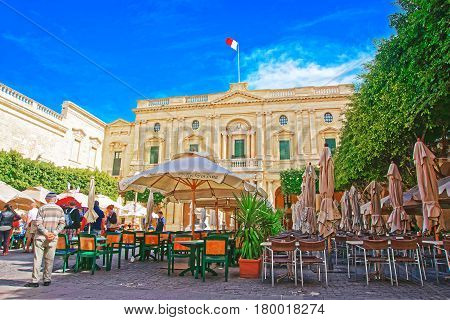 People Resting At Open Air Cafes Of Republic Square Valletta