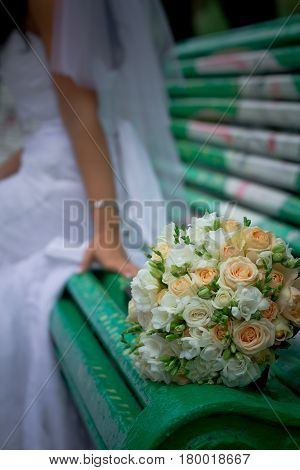The bride's bouquet lies on a green bench against the backdrop of a woman's silhouette in a wedding dress. The bride sits on a bench and looks at her bouquet.