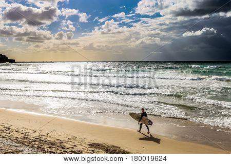 Surfer man on beach at sunset holding bodyboard. Summer holidays vacation on tropical beach. Mediterranean sea Tel Aviv Israel.