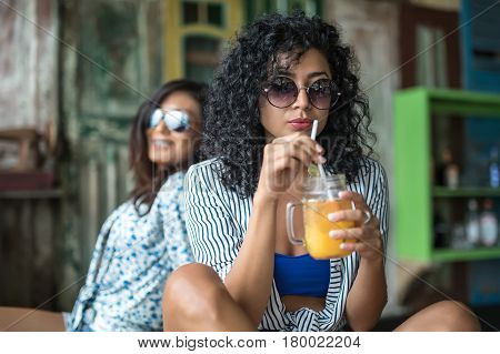 Beautiful girls sit in the bar on the multicolored wall background. They wear the light shirts with patterns and sunglasses. Curly woman holds a cocktail glass. Closeup low aperture photo. Horizontal.