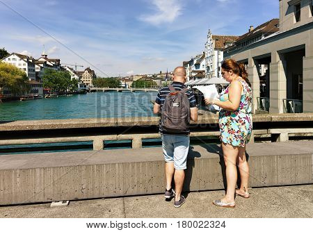People With City Map In Limmat River Embankment Zurich
