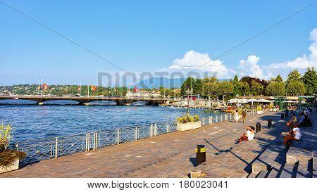 People Sitting On Embankment At Geneva Lake In Summer