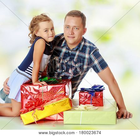 Cute little girl with her favorite dad, sitting on the floor surrounded by a variety of beautifully packaged boxes with gifts.Summer white green blurred background.