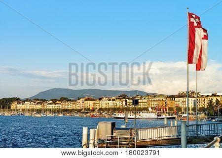 Pier with Swiss flags at Geneva Lake near Promenade du Lac in summer Geneva Switzerland.