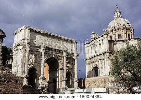 Ancient Arch of Septimius Severus and Saints Luca e Martina baroque church in Roman Forum with cloudy sky