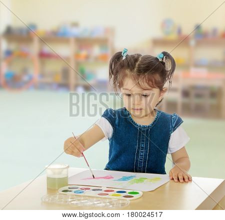 Cute little girl draws with watercolors on a sheet of white paper . Girl sitting at the table.In the Montessori room the children's garden where there are shelves with toys and material.