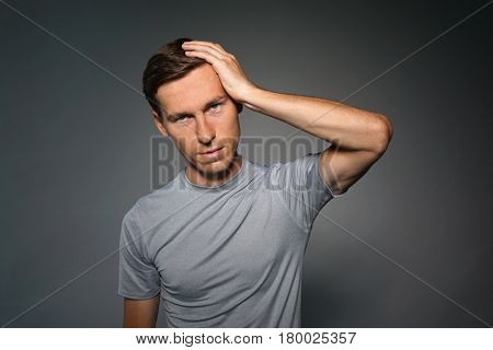 Young man suffering from a headache, a gesture of annoyance.