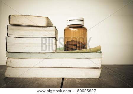 Close up pills in bottle on books