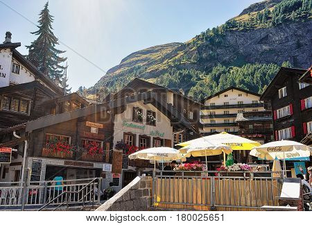 Street With Wooden Traditional Swiss Chalets In Mountains In Zermatt
