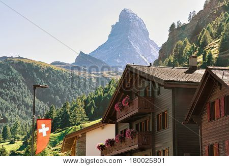 Traditional Chalets In Zermatt With Matterhorn Peak With Swiss Flag