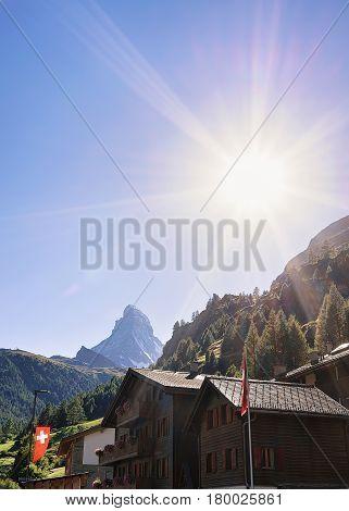Traditional Swiss Chalets In Zermatt With Matterhorn Summit With Flag