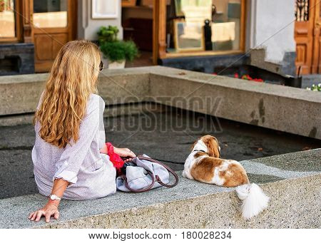 Blonde woman with a dog relaxing in the shade in Montreux Vaud canton Switzerland