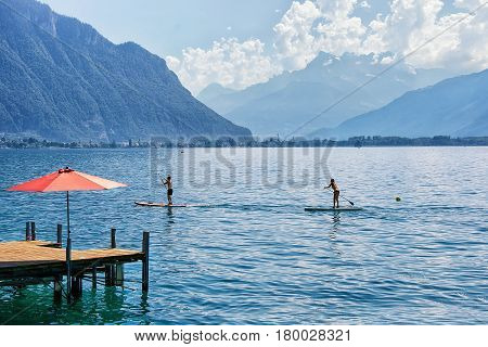 Couple with Standup paddle board on Geneva Lake in Montreux Vaud canton Switzerland