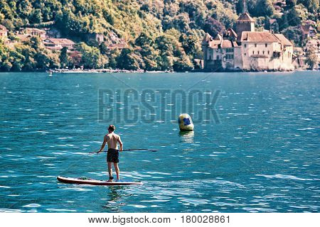 Man Standing On Standup Paddle Surfing On Geneva Lake Montreux