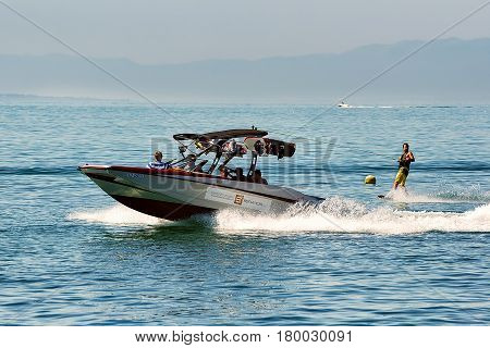 Motor Boat With Man Wakeboarding On Lake Geneva In Lausanne