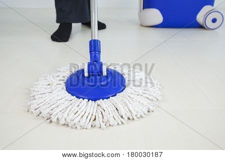 Woman Legs With Mop And Bucket Cleaning Floor