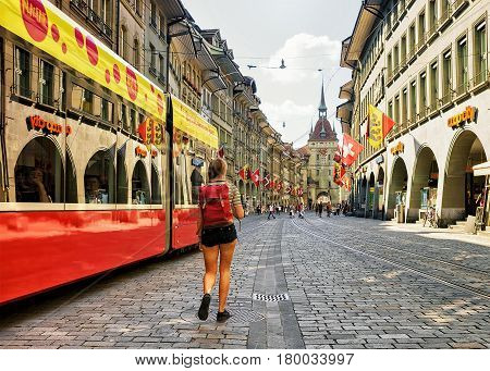 Bern Switzerland - August 31 2016: Girl with backpack and running tram and other people at Kafigturm tower on Marktgasse street with shopping area in old city center of Bern Switzerland