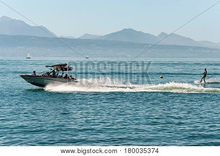 Motor Boat With Man Wakeboarding In Lake Geneva In Lausanne