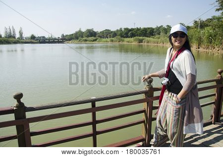 Asian Thai Woman Posing And Travel Looking Crocodiles At Bueng Boraphet Public Park