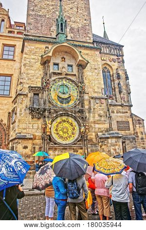 People With Umbrellas At Clock Of Old Town Hall Prague