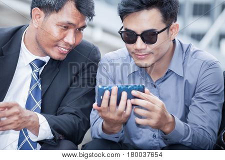 Asian businessman sitting and looking at smartphone that his colleagues presentation and discussion together business concept background