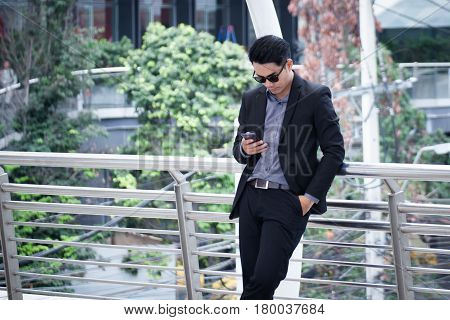 Asian Business Man Standing And Use Smartphone With Business Building Background