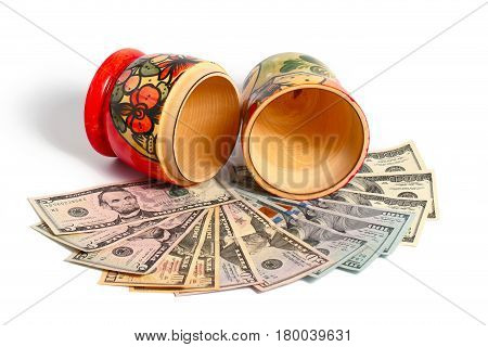 Russian national wooden toy stands on a pile of American dollars